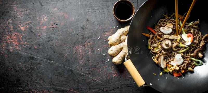 Nouilles parfumées de soba dans une casserole de wok avec des champignons et des légumes frais images libres de droits