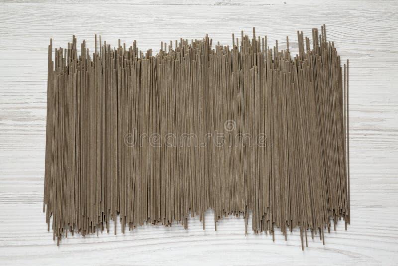 Nouilles sèches de soba de sarrasin sur un fond en bois blanc, vue supérieure Configuration plate, a?rienne, d'en haut photo stock