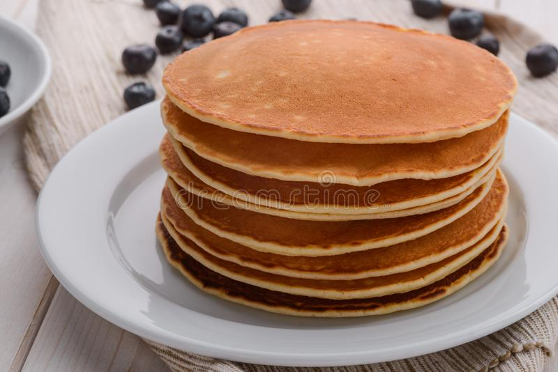A nourishing breakfast. A stack of pancakes on the white plate. Berries are scattered over the table. A nourishing meal. Breakfast in American style royalty free stock photography