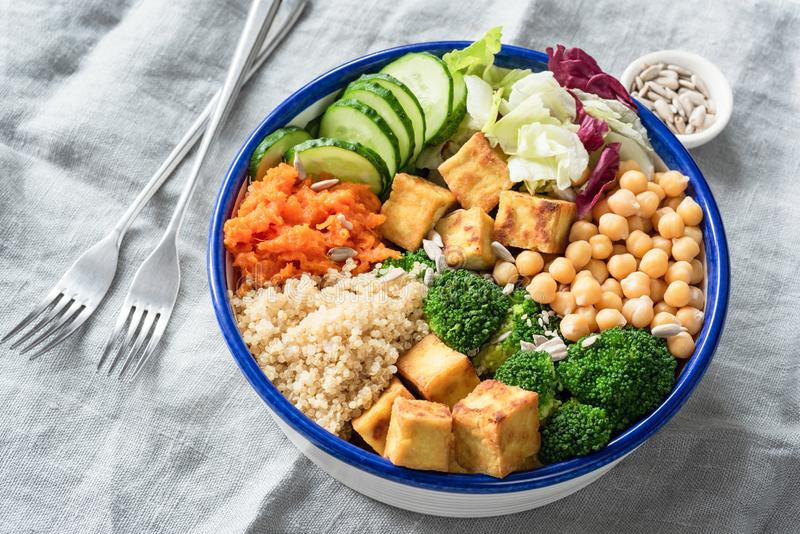 Nourishing buddha bowl with tofu, quinoa and vegetables. Healthy eating, healthy lifestyle, vegan food, vegetarian diet, modern lifestyle concept. Colorful royalty free stock images