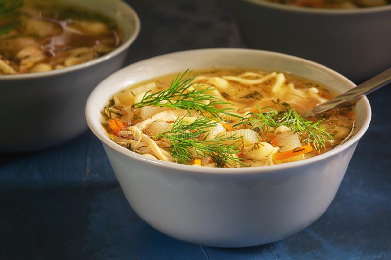 Nourishing Chicken Noodle Soup White Bowl Closeup. Full Dish of Starter Meal. Healthy Family Recipe. Poultry Bouillon with Chopped Veggies and Herbs. Warm stock image