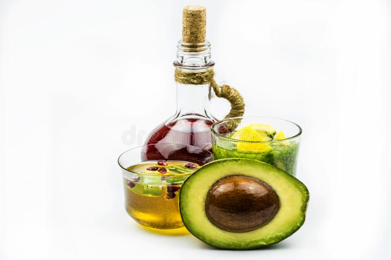 Nourishing face mask in glassware, avocado, pomegranate juice, lemon, honey isolated on a white background. Plants with a therapeutic effect used in cosmetology stock photography