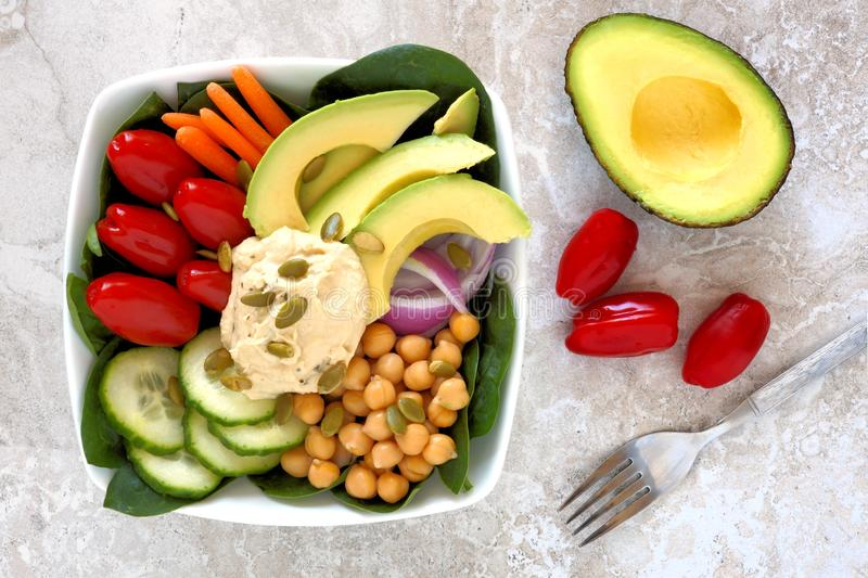 Nourishment bowl with avocado, hummus and mixed vegetables. Healthy nourishment bowl with avocado, hummus and mixed vegetables, overhead scene on white marble stock photography