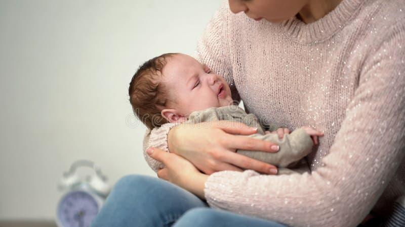 Nourrisson pleurant apaisant de maman, probl?mes avec tomber nuit endormie et sans sommeil image stock