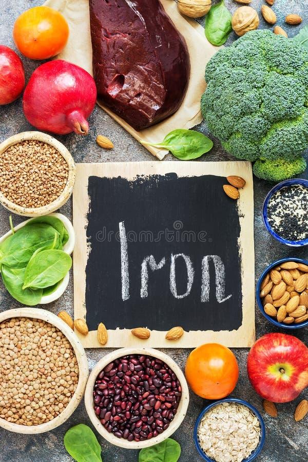 Nourriture avec du fer, foie, grenade, écrous, kaki, pommes, haricots, lentilles, brocoli, sarrasin, épinards, sésame sur un dos  photographie stock libre de droits