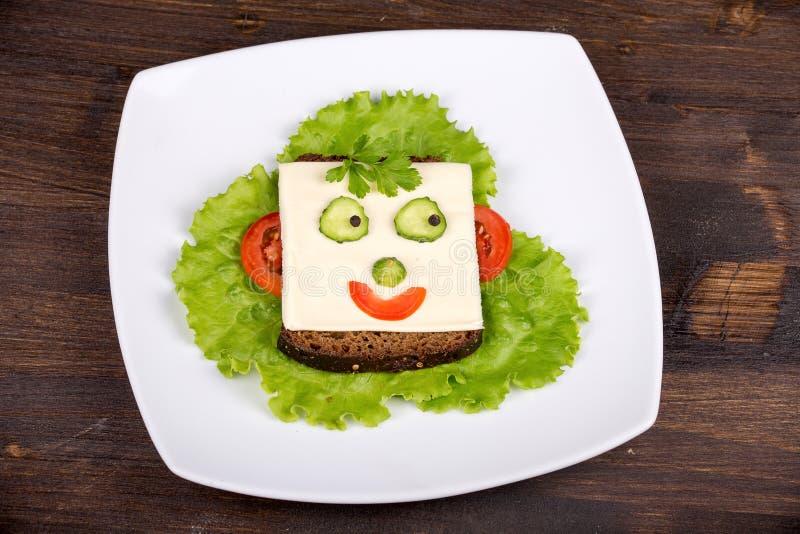 Nourriture d'amusement pour des enfants - visage sur le pain photographie stock