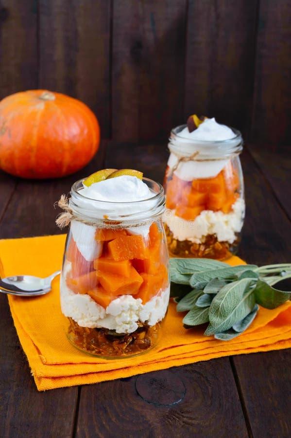 Nourriture dans un pot : granola avec des écrous, fromage blanc, tranches de potiron bouilli, mascarpone photos libres de droits