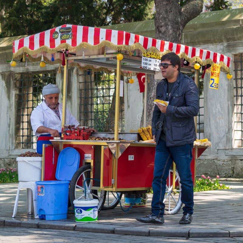 Nourriture de achat de touristes d'un chariot turc traditionnel de châtaigne et de maïs en Sultan Ahmed Square, Istanbul, Turquie image stock