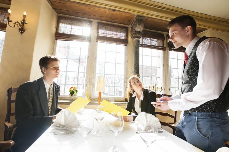 Nourriture de commande de couples d'affaires à la table de restaurant images libres de droits