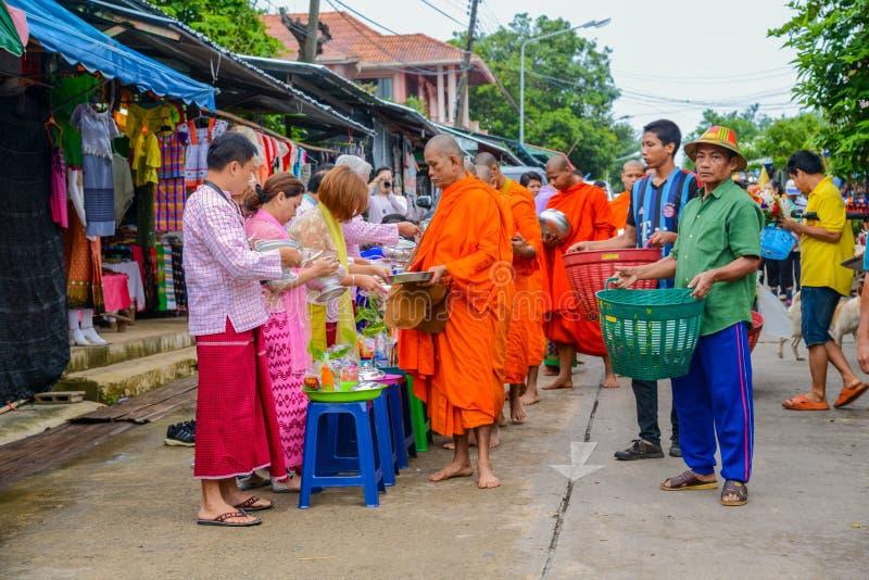 Nourriture de offre et choses de personnes au groupe de moines bouddhistes images stock