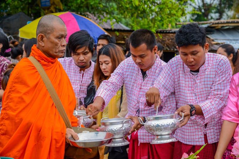 Nourriture de offre et choses de personnes au groupe de moines bouddhistes photo stock