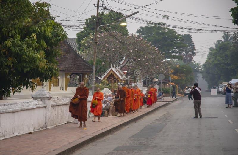 Nourriture de offre de touristes au moine dans Luang Prabang images stock