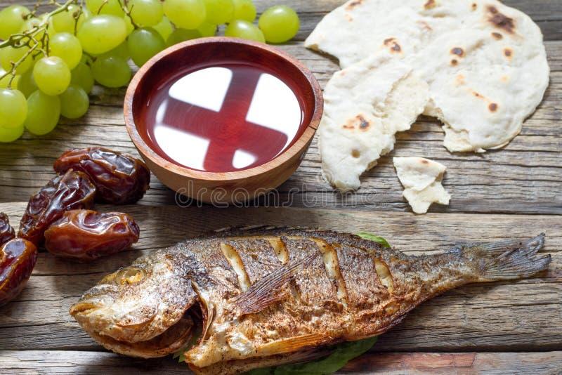 Nourriture de Pâques avec la croix de pain de pâque de poissons dans le gobelet de l'abrégé sur dernier dîner de vin image libre de droits