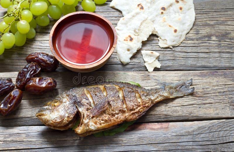 Nourriture de Pâques avec la croix de pain de pâque de poissons dans le gobelet de l'abrégé sur dernier dîner de vin photographie stock