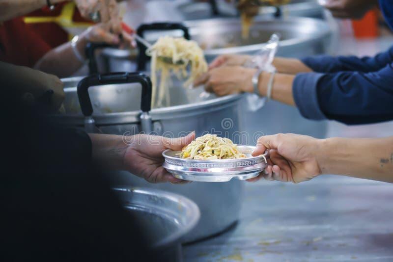 Nourriture de part de volontaires aux pauvres pour soulager la faim : Concept de charité photographie stock