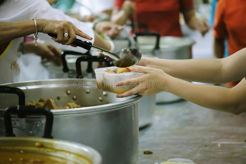 Nourriture de part de volontaires aux pauvres pour soulager la faim : Concept de charité images libres de droits