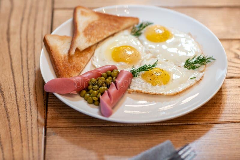 Nourriture de petit déjeuner Petit déjeuner américain de style avec des oeufs au plat, saucisse, pois et griller le concept d'un  photographie stock libre de droits