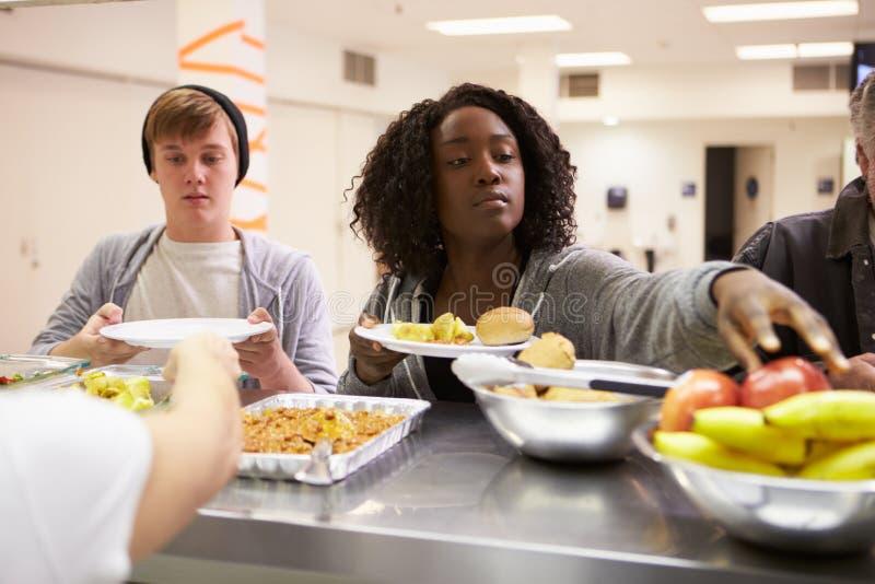 Nourriture de portion de cuisine dans le foyer pour sans-abris image libre de droits