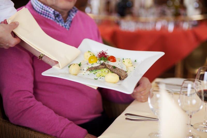 Nourriture de portion de la main du serveur au client masculin au Tableau de restaurant photos stock