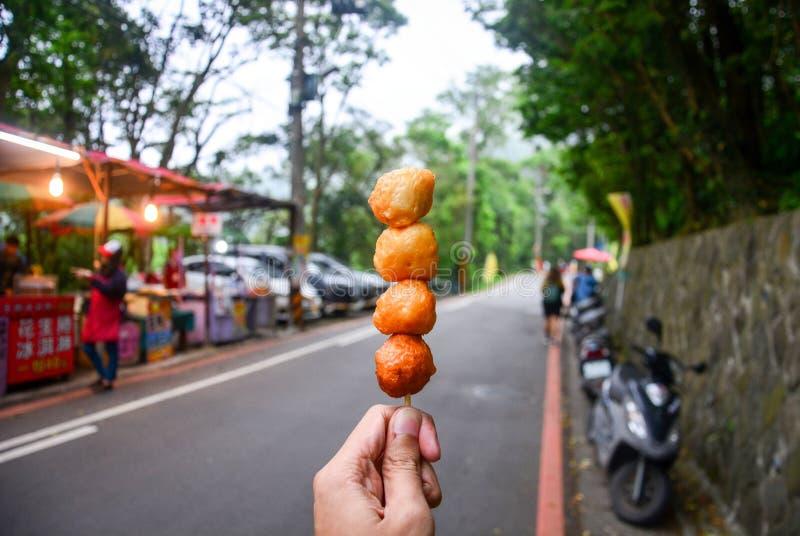 Nourriture de rue, main tenant la boule de crevette cuite à la friteuse sur la brochette en bois avec le fond de stalle de nourri images libres de droits