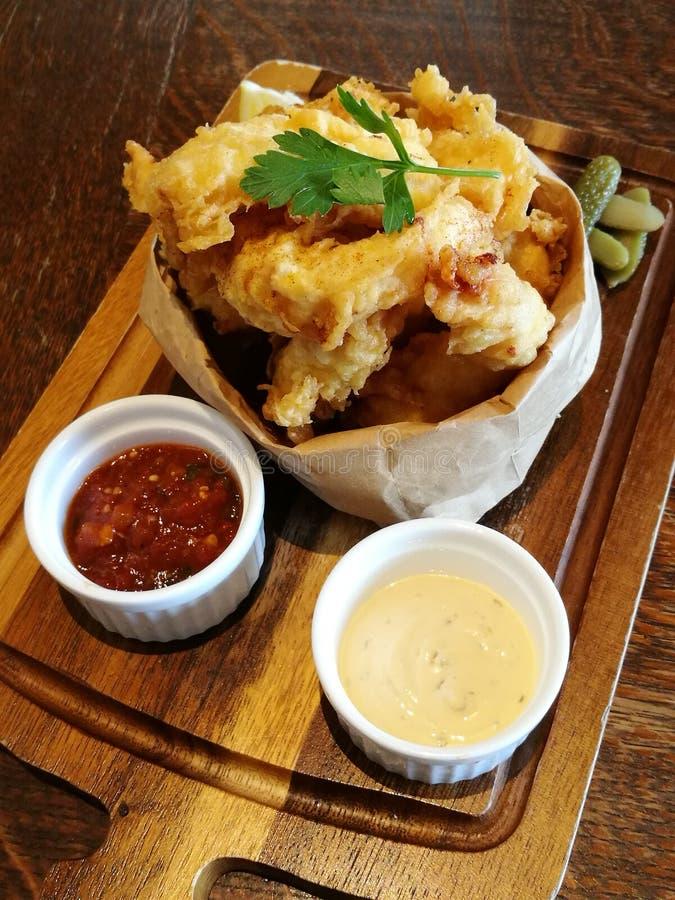Nourriture de styliste, calamari cuit à la friteuse sur le sac de papier avec le service de sauce à piments et de mayonnaise ou d image libre de droits