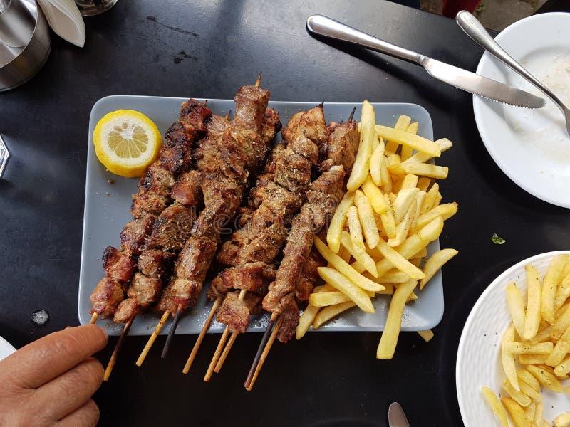 Nourriture ethnique grecque de Souvlaki ou de souvlakia de plat r?ti de viande avec les pommes de terre et le citron images libres de droits