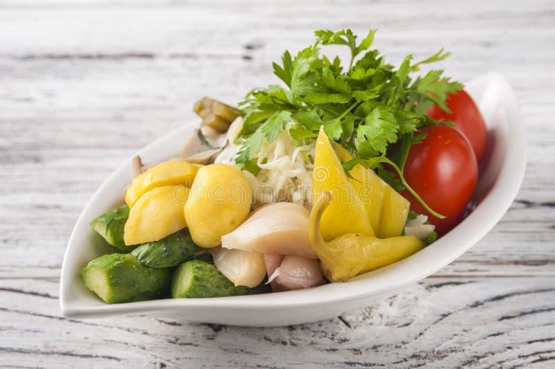 Nourriture fermentée dans un plat sur une table en bois de texture blanche Concombres, courgette, ail, marinade, tomates, chou, r image stock