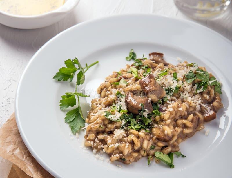 Nourriture italienne Risotto avec les champignons et le fromage d'un plat blanc sur un fond blanc photos stock