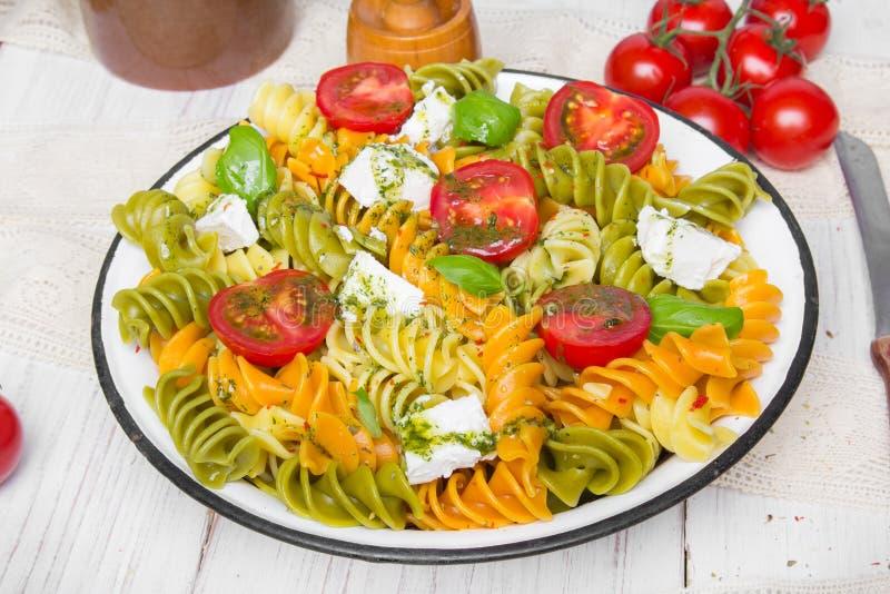 Nourriture italienne - salade avec les pâtes colorées, les tomates-cerises, le feta et le basilic frais image libre de droits