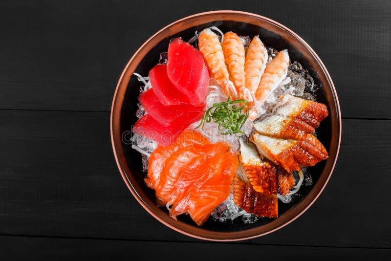 Nourriture japonaise de sashimi, morceaux de thon, saumon, langoustine, anguille fumée avec de la glace dans la cuvette sur le fo photographie stock libre de droits