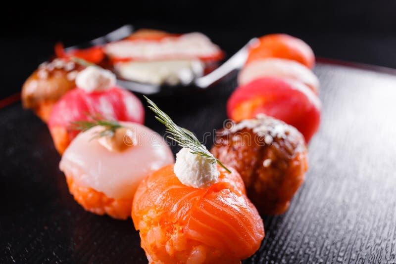 Nourriture japonaise, savoureuse du repas pour le déjeuner Fruits de mer Sushi avec l'anguille, saumon, truite, fond noir de thon photo libre de droits
