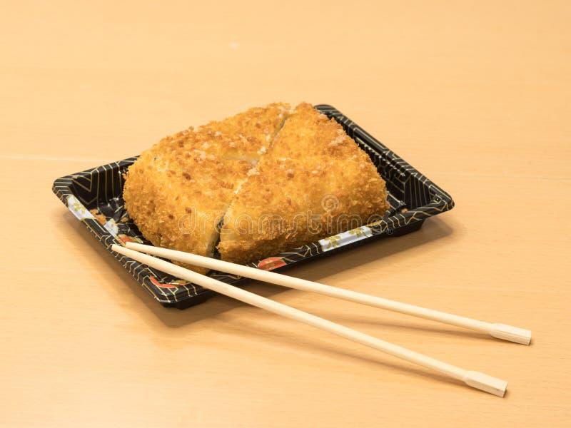Nourriture japonaise traditionnelle - les sushi grillent, coupent en quatre morceaux avec les baguettes en bois sur un plateau image stock