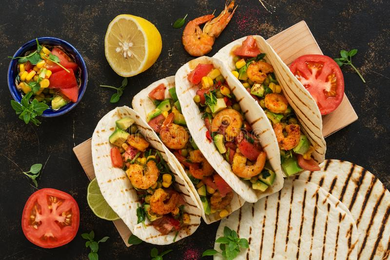 Nourriture mexicaine Tacos fait maison avec de la sauce à crevette, à avocat et à Salsa sur un fond rustique foncé supplémentaire photos libres de droits