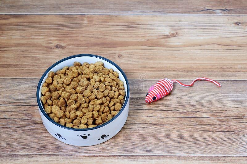 Nourriture sèche de chat chez une souris de cuvette et de jouet Sur le fond en bois brun images stock