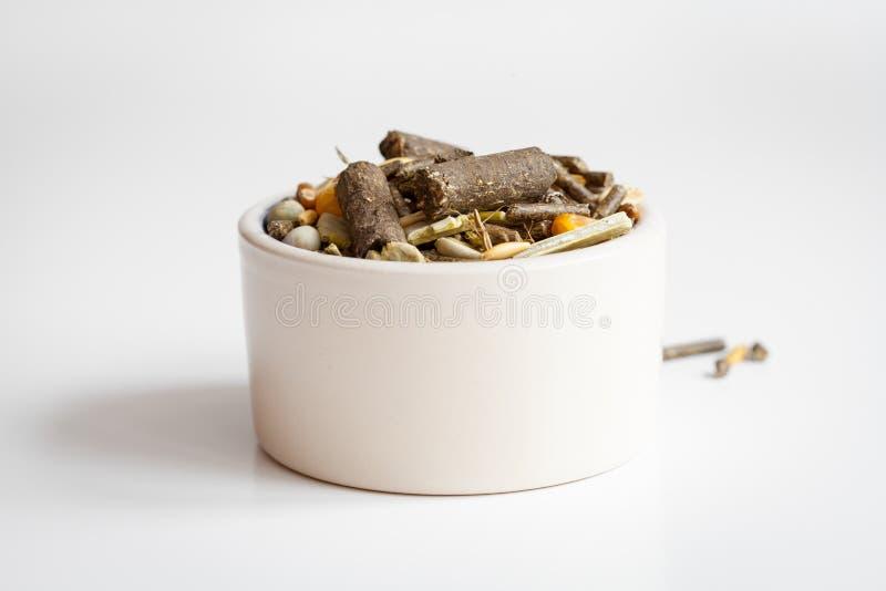 Nourriture sèche pour des rongeurs à l'arrière-plan de blanc de cuvette images libres de droits