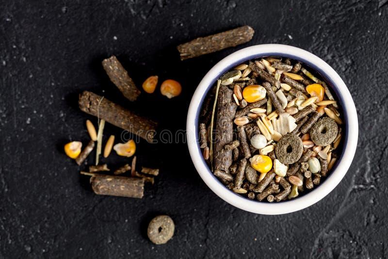 Nourriture sèche pour des rongeurs dans la vue supérieure de fond foncé de cuvette images stock