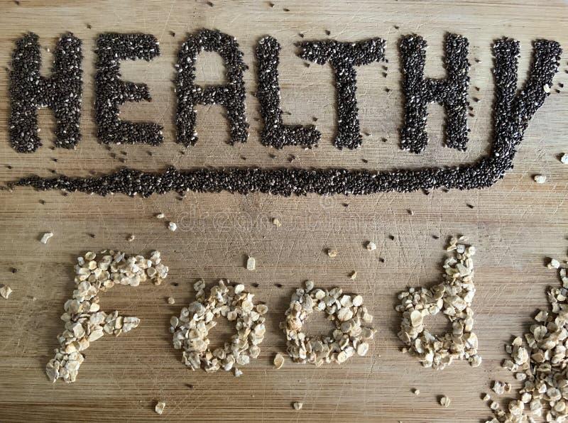 Nourriture saine écrite avec le chia et l'avoine sur un conseil en bois Bannière végétale images stock