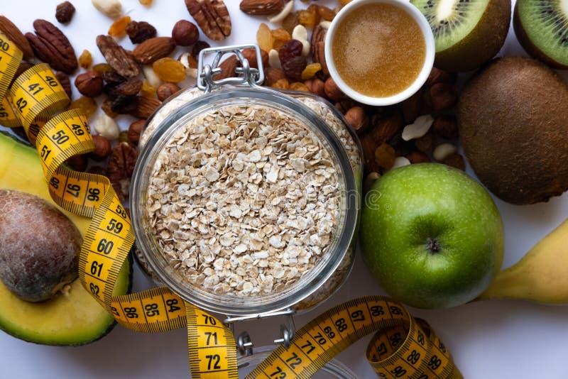 Nourriture saine et concept de forme physique Fruits frais, écrous et céréale sur le fond blanc images libres de droits