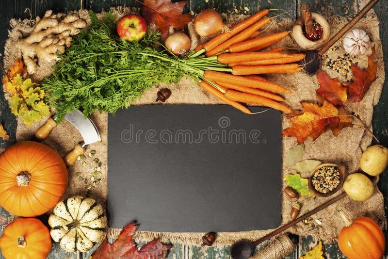 Nourriture saine faisant cuire le fond Carottes, potirons, oignons, pommes et épices frais de jardin sur le fond rustique images stock