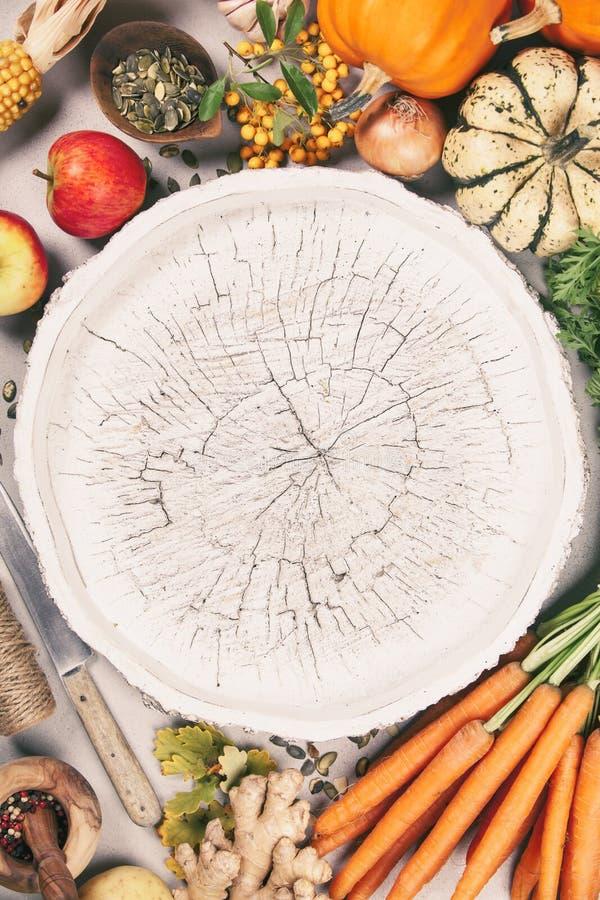 Nourriture saine faisant cuire le fond Carottes, potirons, oignons, pommes et épices frais de jardin sur le fond rustique photo libre de droits