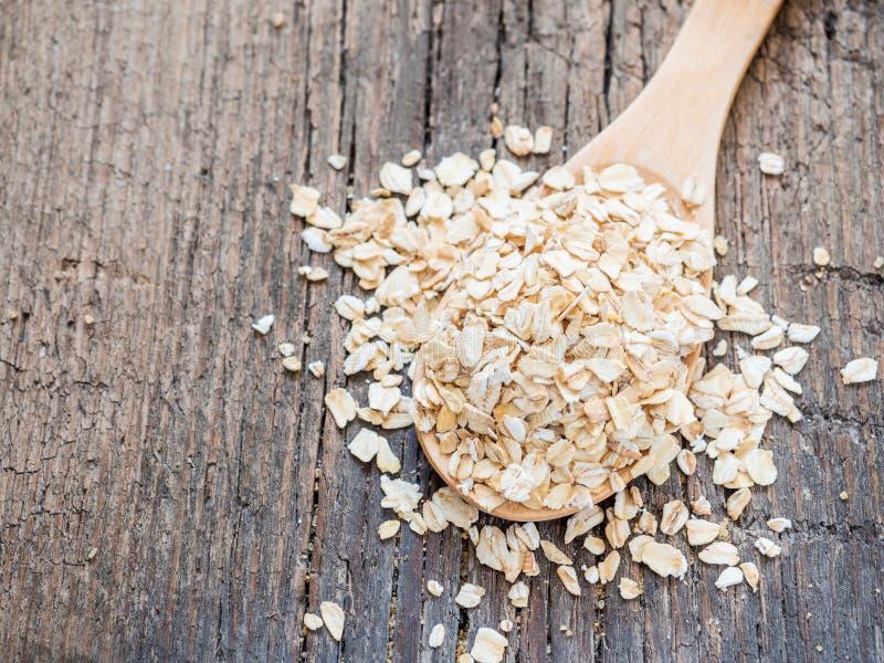 Nourriture saine Flocons d'avoine secs dans la cuillère sur le fond en bois closeup image stock