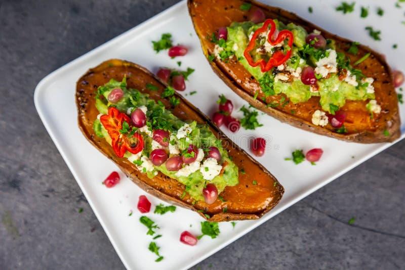Nourriture saine - les patates douces cuites au four ont servi avec le guacamole, le feta et la grenade image stock