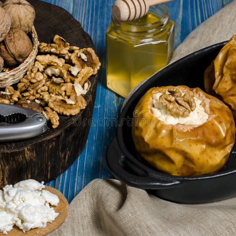 Nourriture saine Les pommes cuites au four avec le fromage blanc et les ?crous se situent dans un plat de cuisson noir sur une ta photos stock
