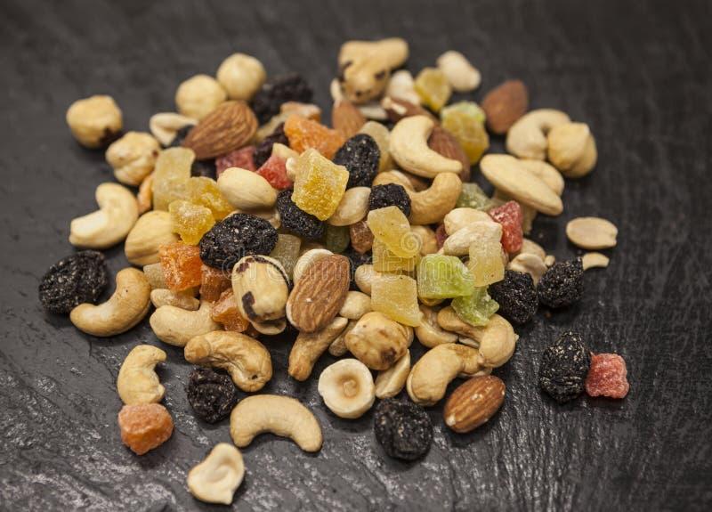 Nourriture saine ; noisettes, amandes, anarcadier, raisin sec et fruits secs sur un fond noir en pierre photo libre de droits