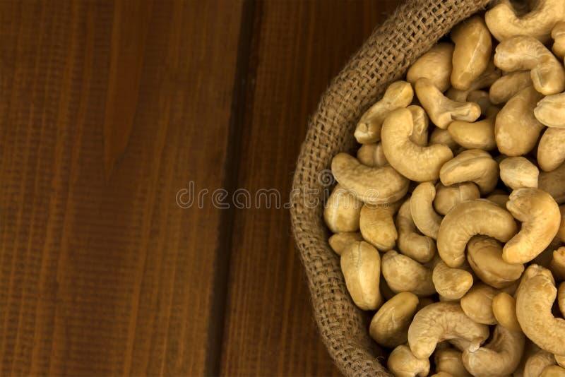 Nourriture saine Noix de cajou dans le sac de sac sur le fond en bois de table image stock