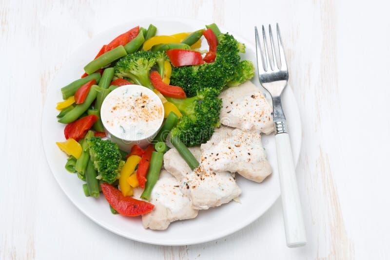 nourriture saine - poulet, légumes cuits à la vapeur et sauce à yaourt photos stock