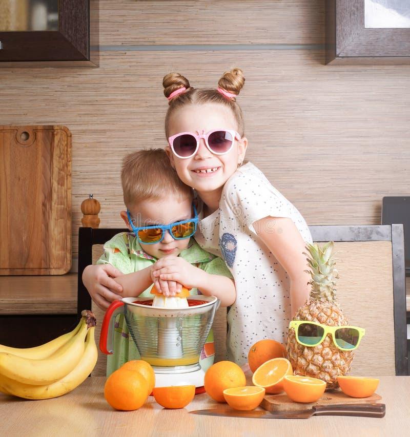 Nourriture saine : une fille et un garçon font le jus d'orange frais photo libre de droits