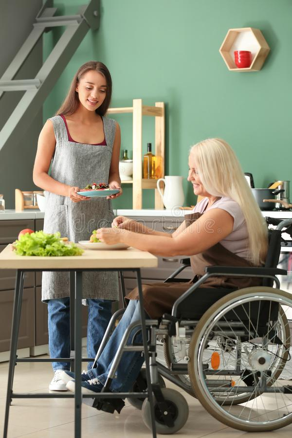 Nourriture servante de jeune femme à sa mère dans le fauteuil roulant à la maison image libre de droits