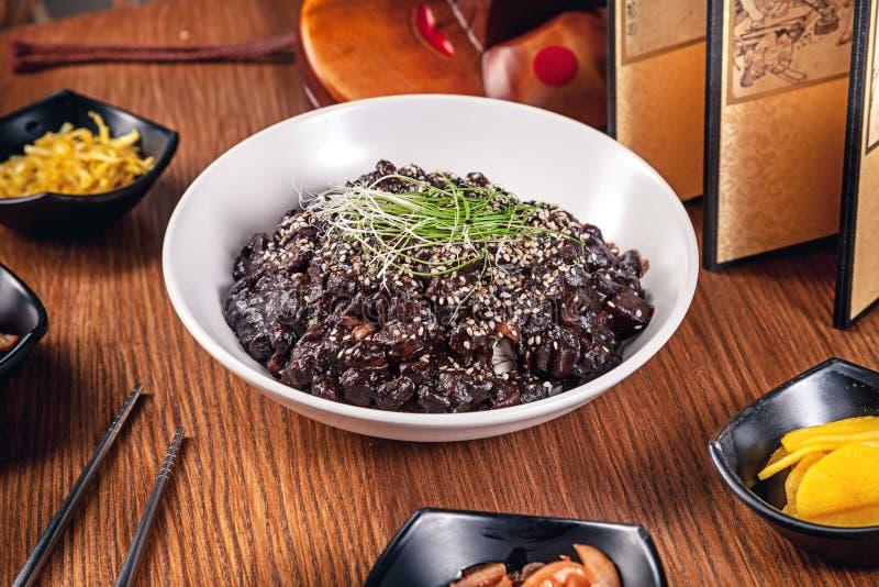 Nourriture traditionnelle coréenne de configuration plate avec le kimchi sur le fond en bois Nouilles noires coréennes de sauce a image stock