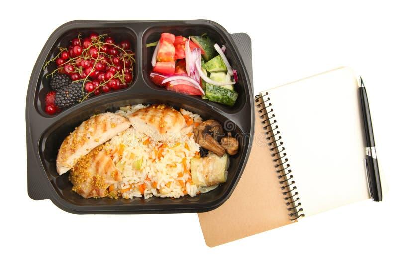 Nourriture utile dans le récipient et le carnet avec le stylo photographie stock libre de droits
